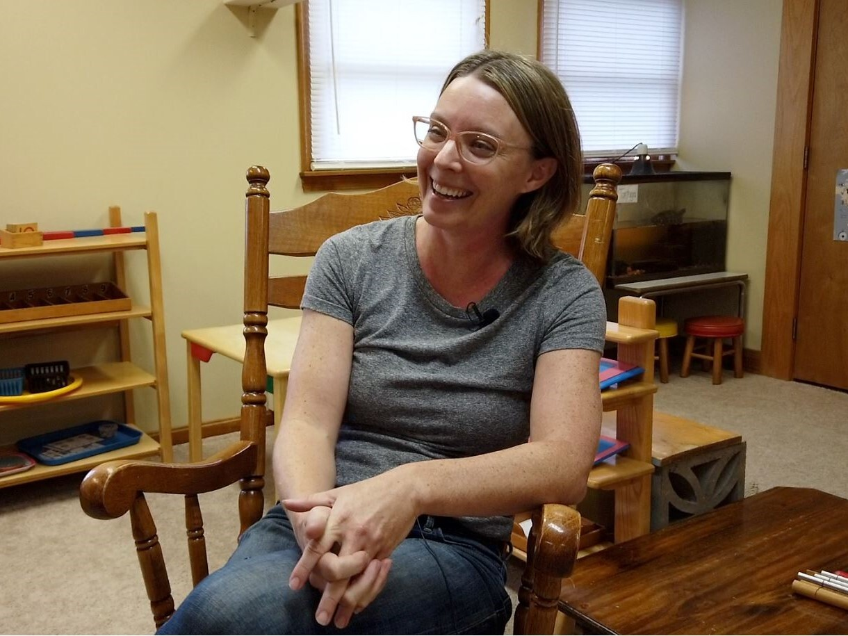 Katie McGoron sits in a rocking chair in the preschool classroom at Shine Nurture Center. She is smiling and had shoulder length, dark blonde hair and glasses.