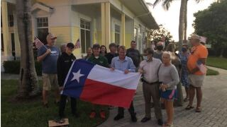 Florida neighbors give flag-waving surprise to young man with special needs