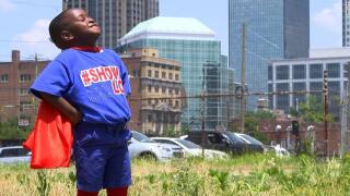 In a superhero cape, he feeds the hungry and homeless. And he's only 4