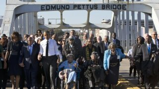 "FILE - In this March 7, 2015, file photo, singing ""We Shall Overcome,"" President Barack Obama, third from left, walks holding hands with Amelia Boynton, who was beaten during ""Bloody Sunday,"" as they and the first family and others including Rep. John Lewis, D-Ga, left of Obama, walk across the Edmund Pettus Bridge in Selma, Ala., for the 50th anniversary of ""Bloody Sunday,"" a landmark event of the civil rights movement. Some residents in the landmark civil rights city of Selma, Ala., are among the critics of a bid to rename the historic bridge where voting rights marchers were beaten in 1965. (AP Photo/Jacquelyn Martin, File)"