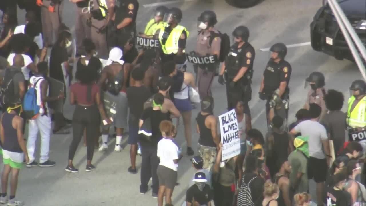 Protesters, including one holding 'black lives matter' sign, confront police on I-95