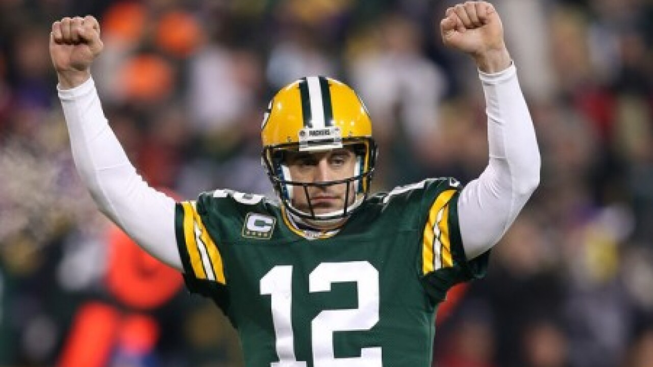 Packers quarterback Aaron Rodgers wearing green jersey and gold helmet