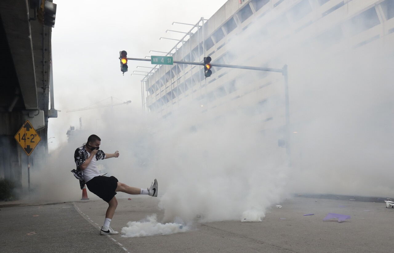Protester kicks tear gas canister back at police in Miami, May 30