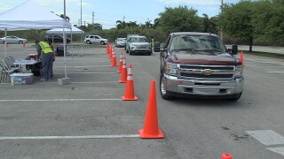 Cars line up at a COVID-19 vaccination site at Anquan Boldin Stadium in Pahokee.jpg