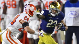 Notre Dame running back Kyren Williams fends off Clemson Tigers safety Nolan Turner in 2020