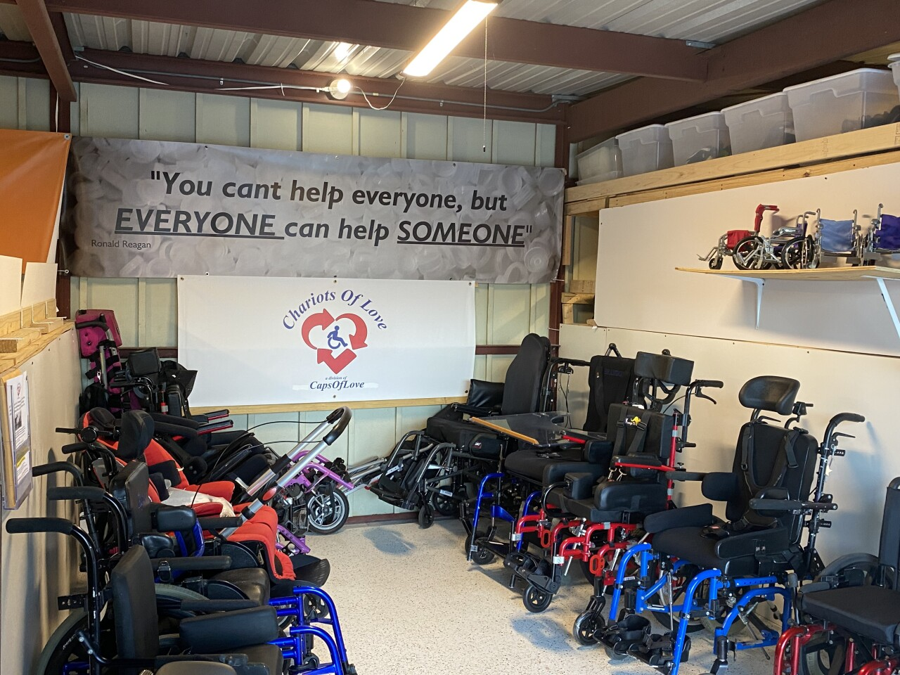 'You can't help everyone, but everyone can help someone' sign in front of 'Chariots of Love' wheelchairs