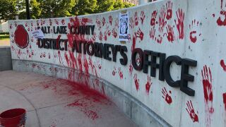 Protesters leave messages at the District Attorney's Office in red paint, chalk, posters