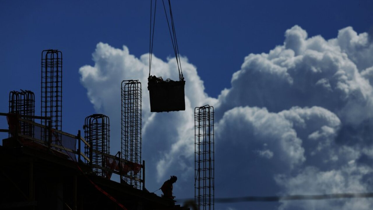 In this July 2, 2019, file photo a construction worker walks atop a building as a crane lifts a load over head in Miami. On Friday, Aug. 2, the U.S. government issues the July jobs report. (AP Photo/Brynn Anderson, File)