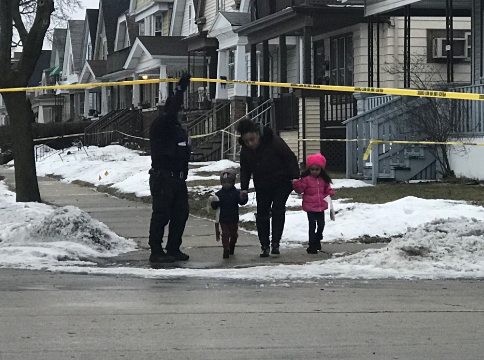 MPD officers escort families who live near 12th and Dakota to and from their homes while police investigate the crime scene