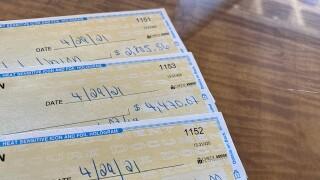 Denver7 Gives checks for Merithew Family bills