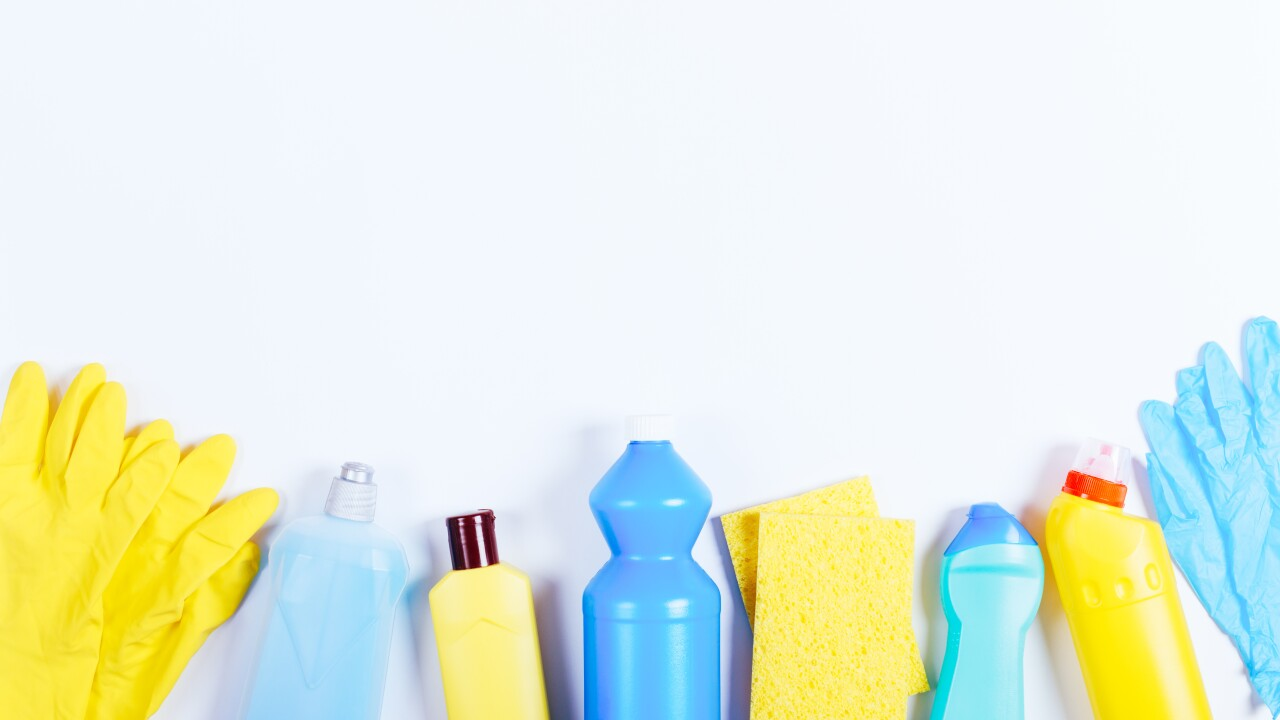 Gloves, sponges, bottles of cleaning fluids on a white table, sp