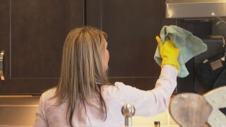 Wendy Flynn, owner of Cleanclean LLC, cleans a cabinet handle.