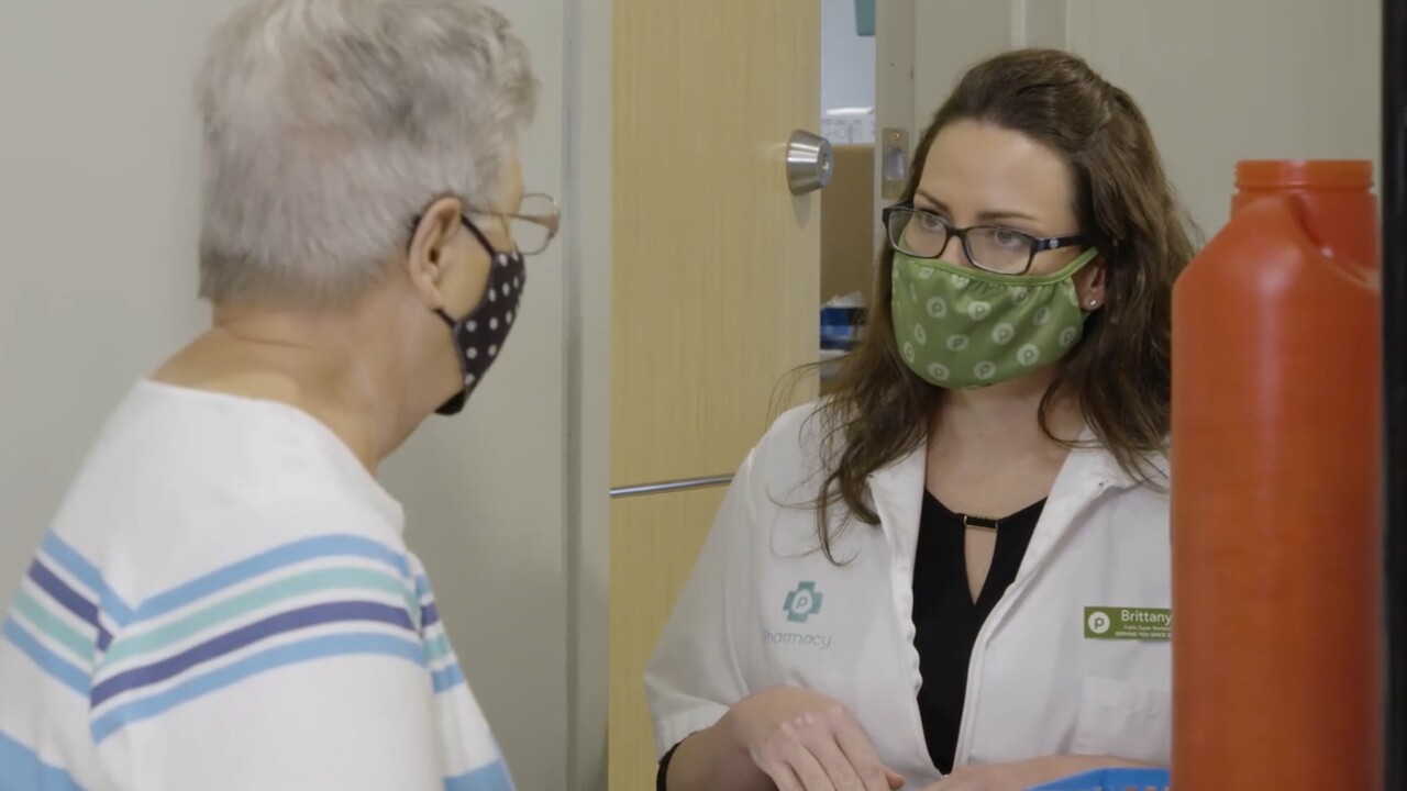 A Publix pharmacist prepares to administer the COVID-19 vaccine to a customer.jpg