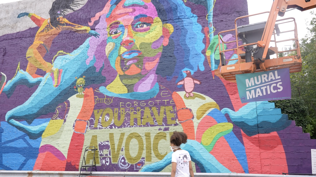 The right side of the mural has a colorful painting of two children who have been working on the mural.
