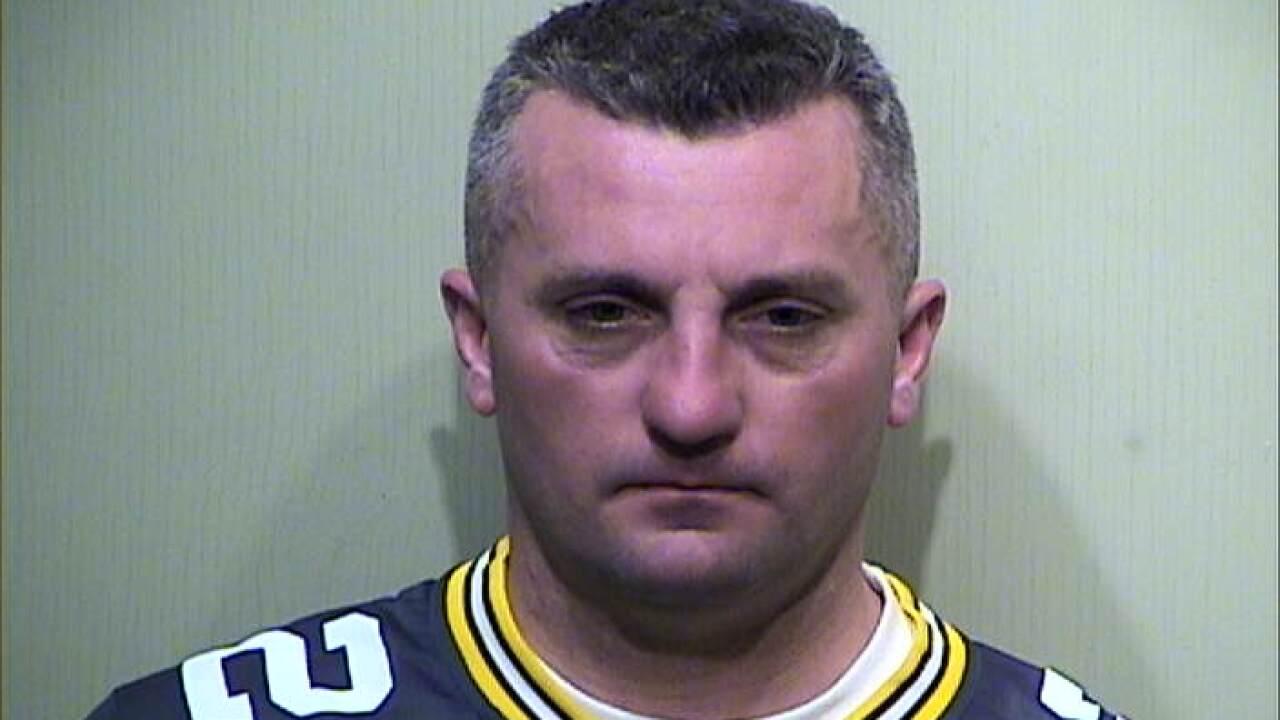 Kenosha Sgt. Greg Munnelly wearing Packers jersey in booking photo