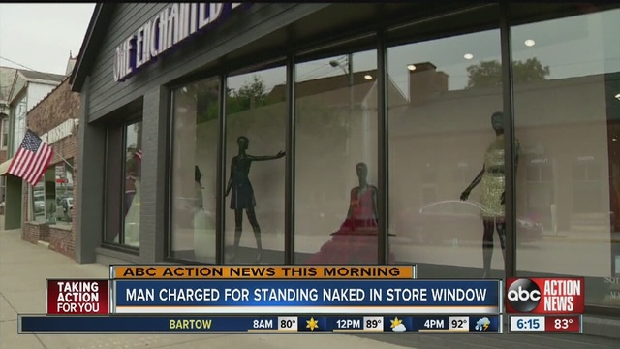 Man charged for standing naked in store window