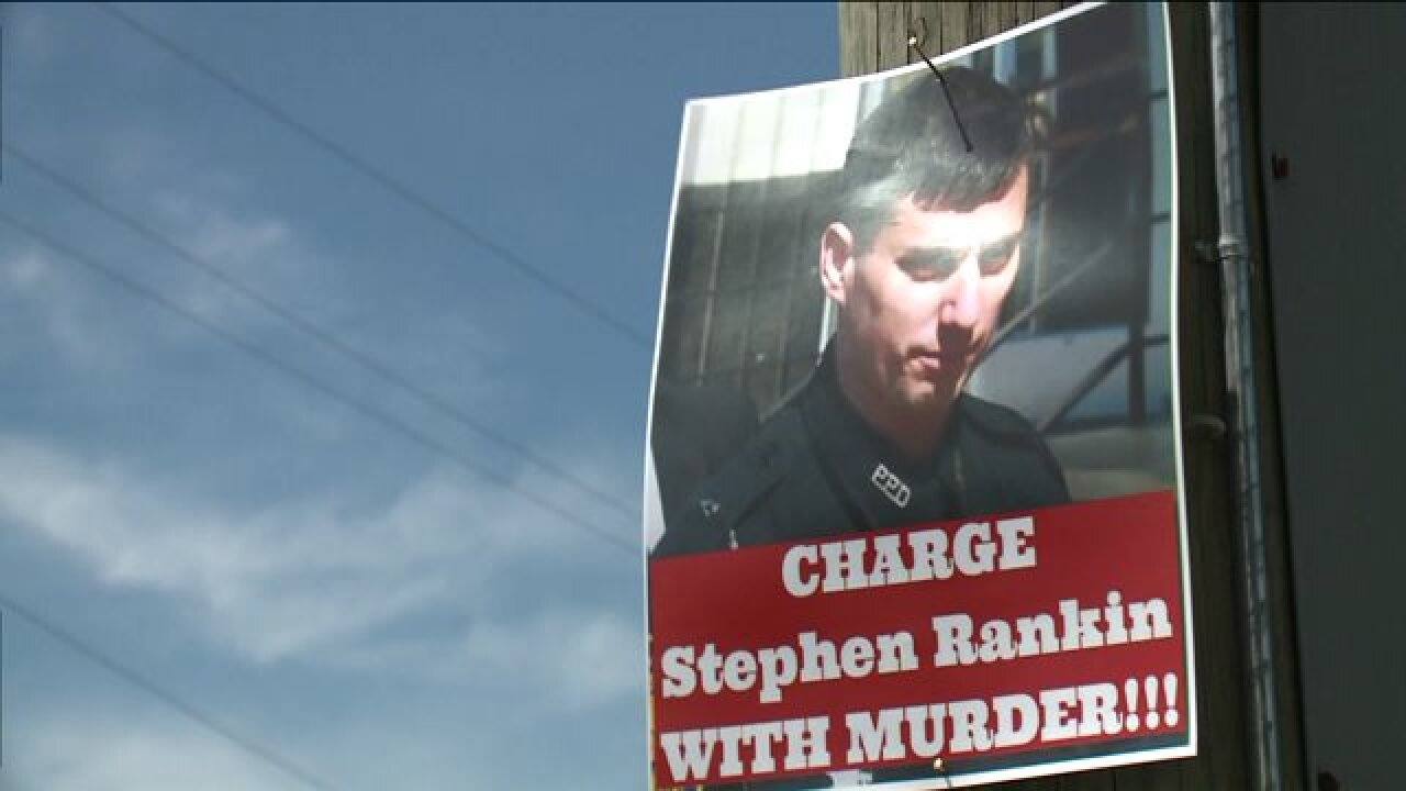Signs demand murder charges against officer who shot teen in Walmart parking lot