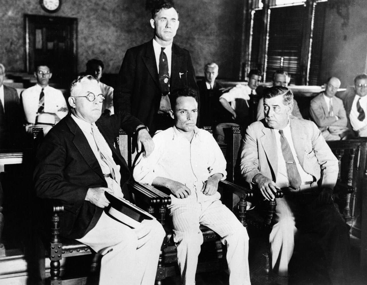 Giuseppe Zangara, Hackensack, N.J. bricklayer, center, is shown in criminal court in Miami, Fla., Feb. 17, 1933, surrounded by unidentified deputies, waiting for arraignment for his attempt to assassinate President-elect Franklin Roosevelt and wounding Chicago Mayor Anton Cermak, and four others, on Feb. 15. Arraignment was postponed. (AP Photo)