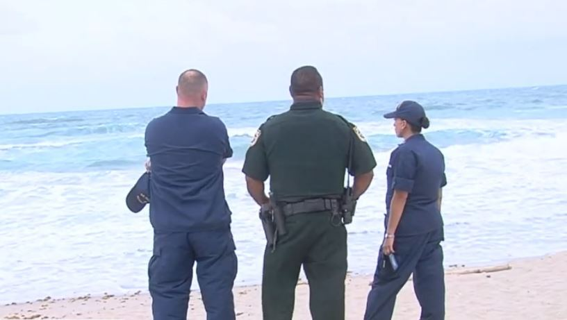 law enforcement stands by water in search for missing swimmer