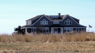 In this April 2, 2019 photo, a multimillion-dollar home sits on a peninsula in Old Saybrook, Conn. The home is among more than 900 structures on the East Coast that would become newly eligible for federal disaster aid, under a proposed remapping of coastal protection zones by the U.S. Fish & Wildlife Service.