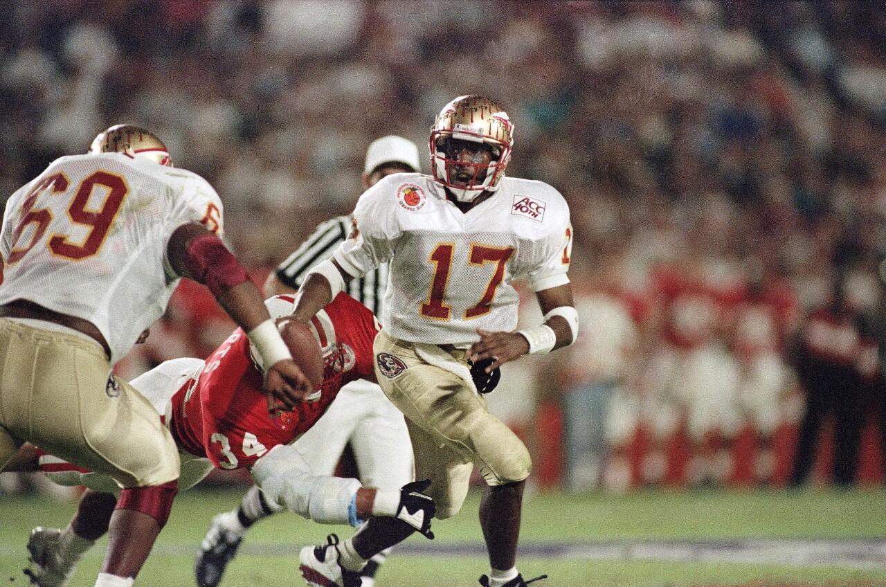 Florida State Seminoles QB Charlie Ward scrambles away from Nebraska Cornhuskers linebacker Trev Alberts in 1994 Orange Bowl