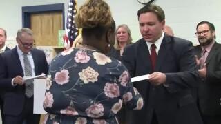 Florida Gov. Ron DeSantis hands out bonus checks to teachers at Lakewood Elementary School in St. Petersburg on Aug. 11, 2021.jpg