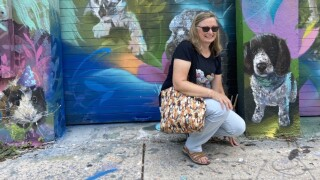 Boynton Beach resident Valerie Johnson kneels next to a painting of her dog at the _Ultimate Pet Portrait_ in Wynwood, organized by the pet supply company Chewy.jpg