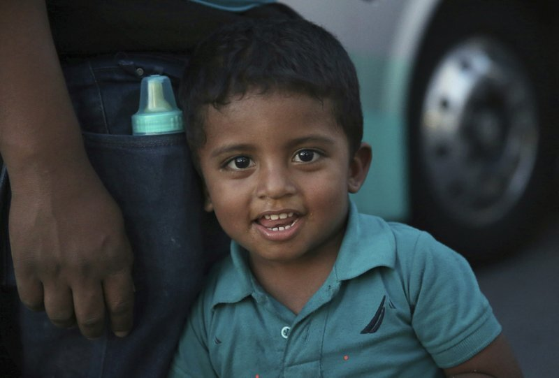 In this July 16, 2019 photo, a migrant child looks at the camera as he waits with his family, outside at an immigration center on the International Bridge 1, to be bused from Nuevo Laredo to Monterret, Mexico. Mexican President Andres Manuel Lopez Obrador's government did not mention the bused migrants Monday when it presented a report halfway into a 90-day period during which it has agreed to reduce irregular trans-migration as part of a deal to head off threatened U.S. tariffs. (AP Photo/Marco Ugarte)