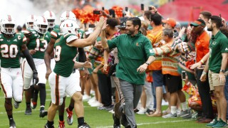 Miami Hurricanes head coach Manny Diaz high fives Jimmy Murphy while running out of tunnel in 2019