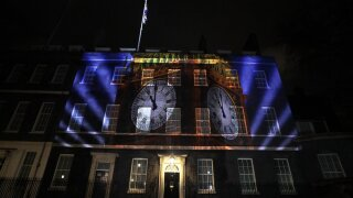 An image of the clock face of 'Big Ben' is projected onto the exterior of 10 Downing street, the residence of the British Prime Minister, in London as Britain left the European Union, Friday, Jan. 31, 2020. With little fuss and not much fanfare, Britain left the European Union on Friday after 47 years of membership, taking a leap into the unknown in a historic blow to the bloc. (AP Photo/Kirsty Wigglesworth)