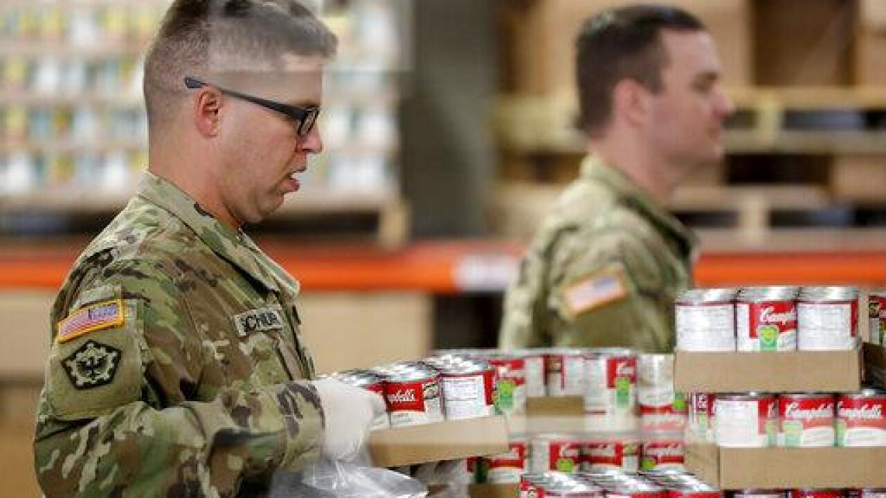 Members of the Arizona National Guard pack and sort food items at a food bank Thursday, March 26, 2020, in Mesa, Ariz. The Guard was at the food bank performing one of their first missions since they were activated by Gov. Doug Ducey to bolster the supply chain for food amid surging demand in response to the COVID-19 coronavirus outbreak. (AP Photo/Matt York)