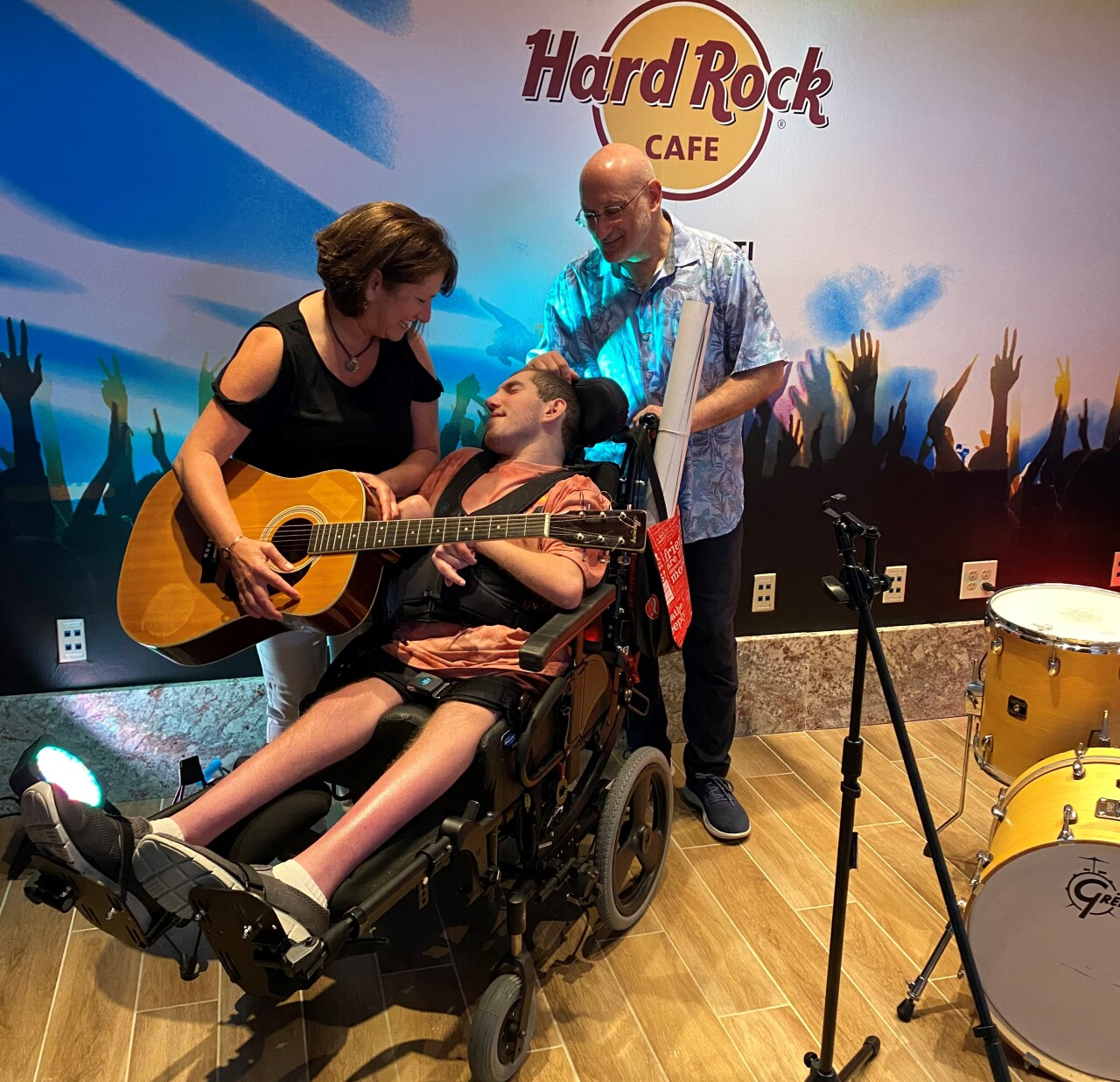 In this photo, Alexia Kadish is holding a guitar near her son, Ethan, who is seated in his wheelchair. Scott Kadish, Ethan's dad, is standing behind Ethan holding the wheelchair.