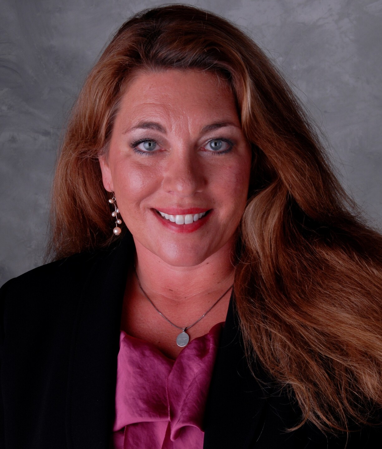 Jeanne Golliher is smiling in this photo. She has blue eyes, long, wavy brown hair and is wearing a mauve blouse and black jacket.