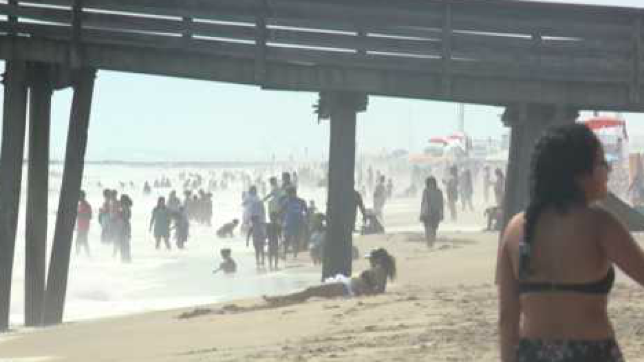 Beachgoers enjoy the sun while officials express concern ahead of Hurricane Dorian