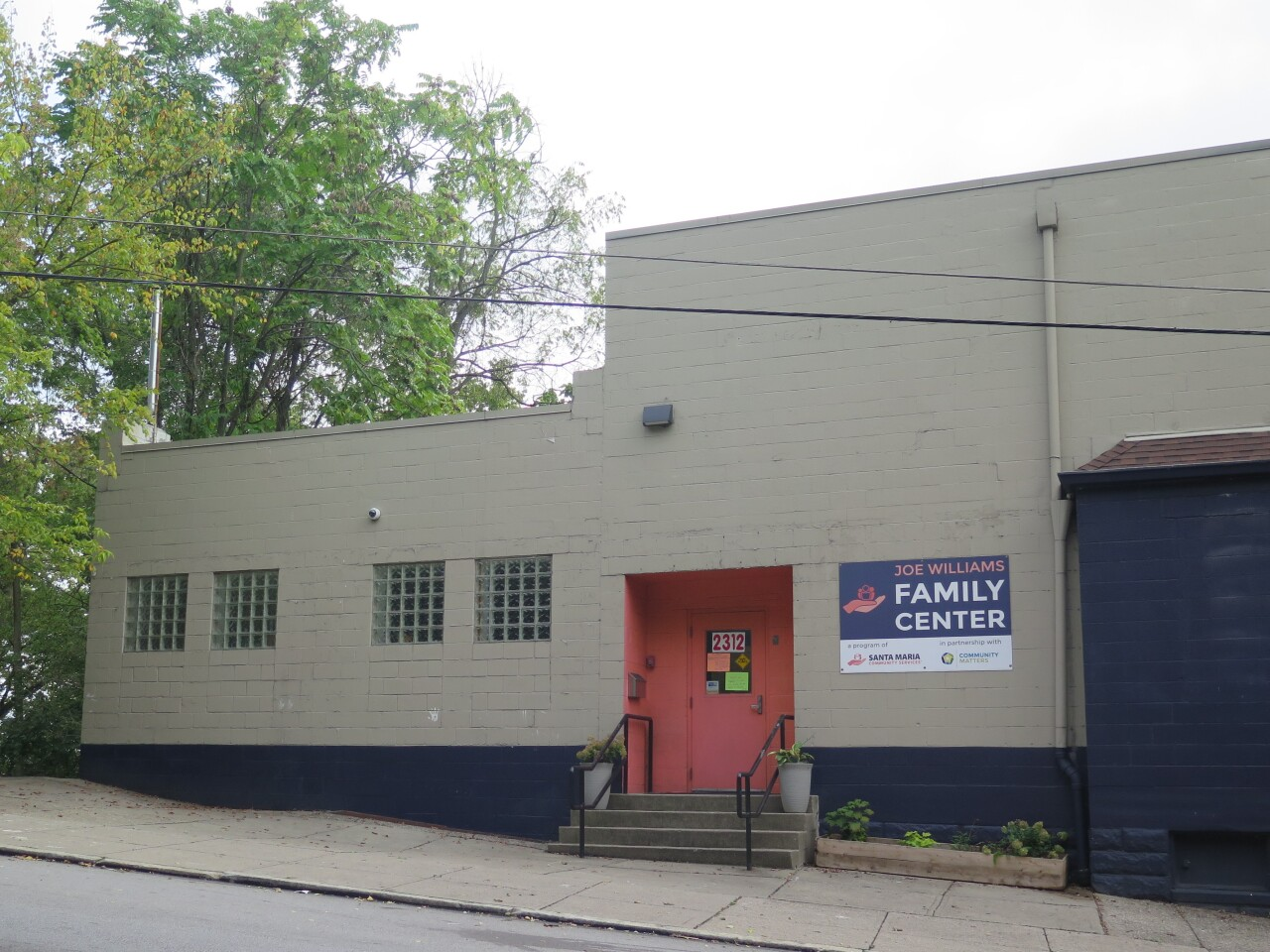 The Joe Williams Family Center in Lower Price Hill is a cinderblock building painted a greyish color with a red door.