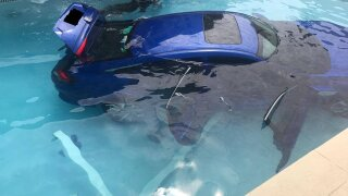 Photos: Woman fails to put car in park, it rolls into swimming pool with husband, child inside