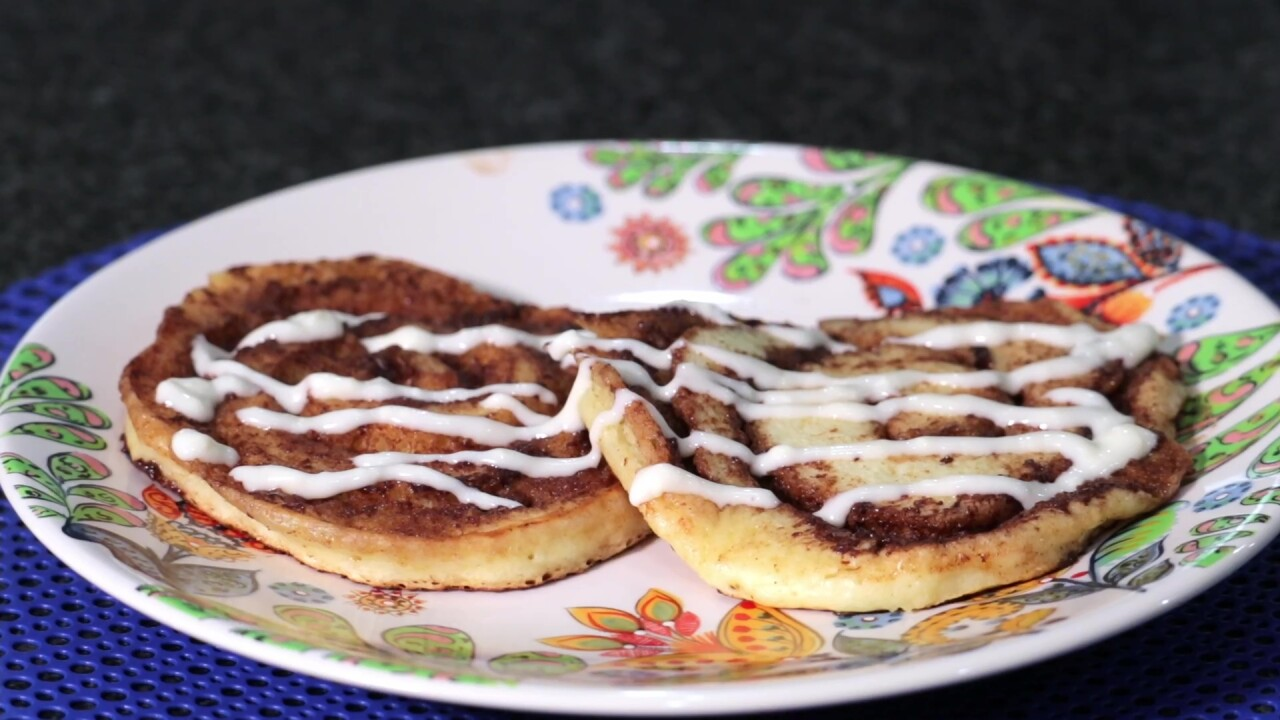 The plated cinnamon roll pancakes with the cream cheese glaze drizzled over it.
