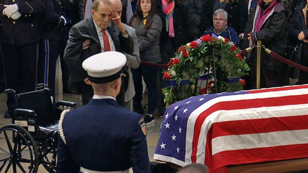 Former Senate Majority Leader Bob Dole salutes former President George H.W. Bush