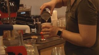 Barista at Third Space Coffee serves a cup of coffee for a customer