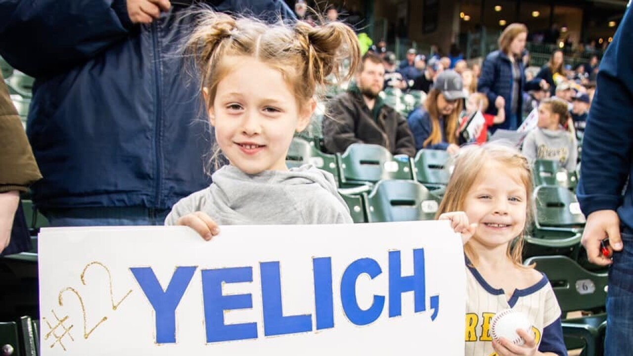 Lola Labodda holds sign for Christian Yelich to hit a homerun