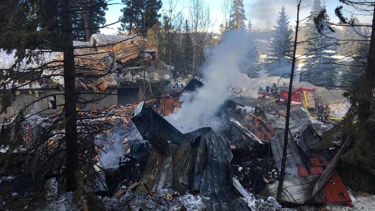 Firefighters take in the blast site of a residence that exploded Sunday