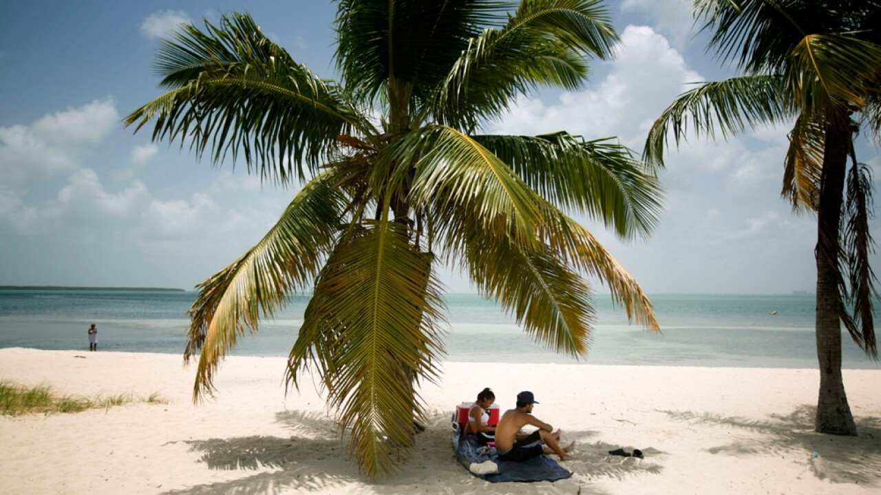In this July 1, 2015 file photo, Marvin Hernandez, right, and Kelly Vera sit in the shade of a palm tree, in Key Biscayne, Fla.