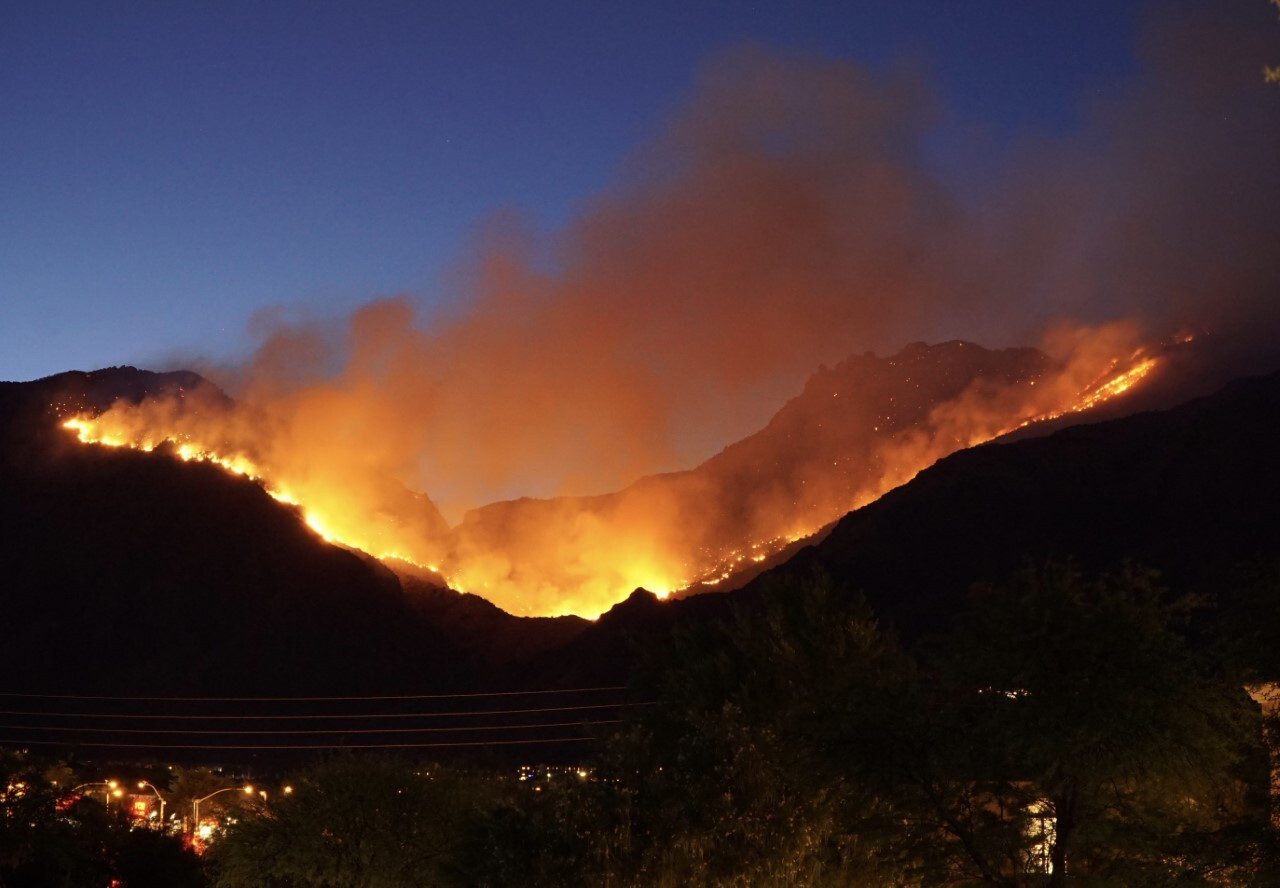 The Bighorn Fire burns steadily in the Catalina Mountains as seen here from behind these structures