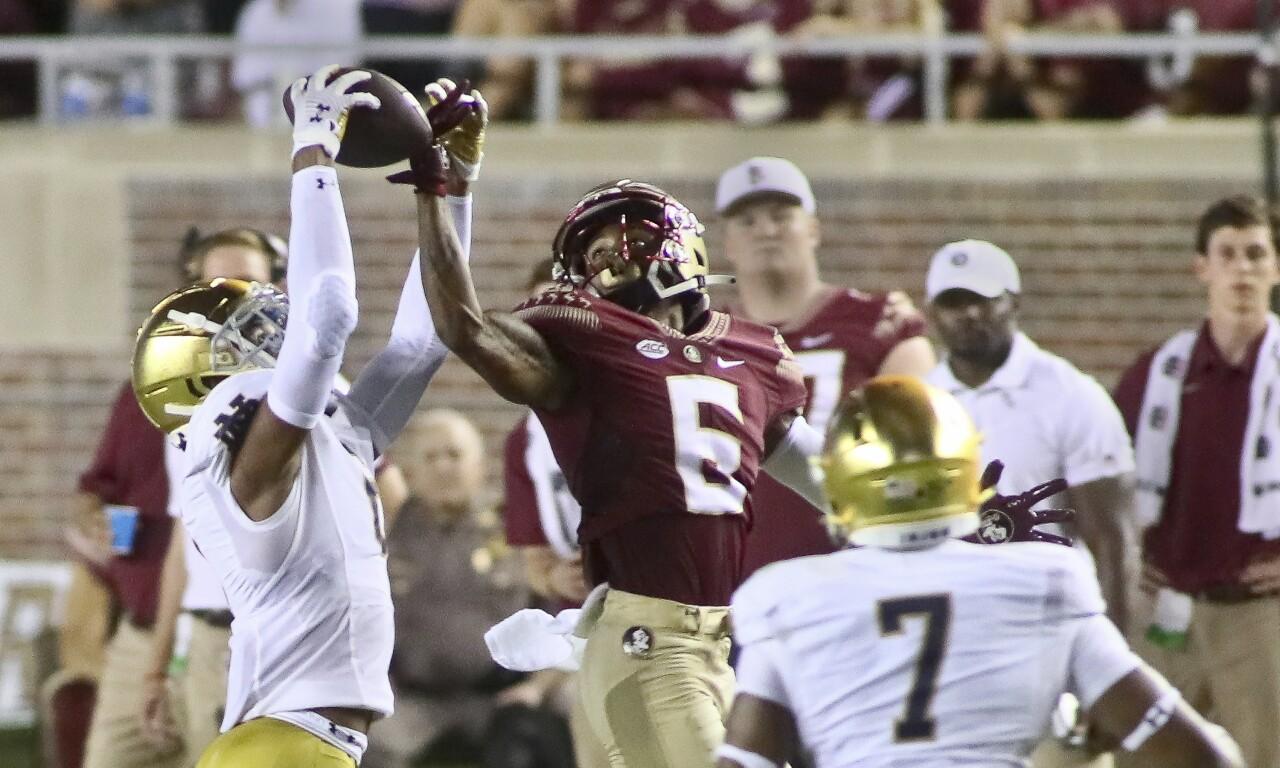 Notre Dame Fighting Irish cornerback Clarence Lewis intercepts pass in front of Florida State Seminoles receiver Keyshawn Helton in 2021