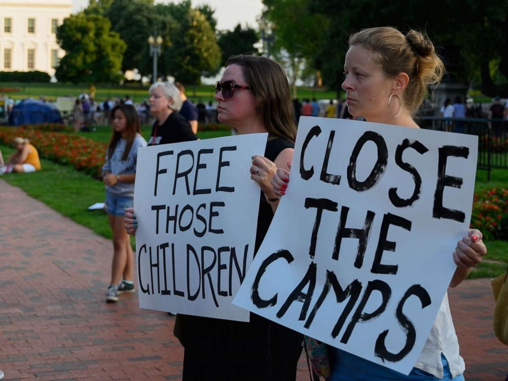 """People hold signs during a """"Lights For Liberty"""" rally to demand Border Patrol facilities and migrant detention centers in the United States to be closed down, at Lafayette Square near the White House in Washington, DC, July 12, 2019. (AP)"""