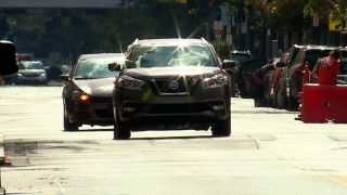 Cars slowly go over a raised crosswalk Tuesday on Vine St. in Cincinnati's Over-the-Rhine neighborhood