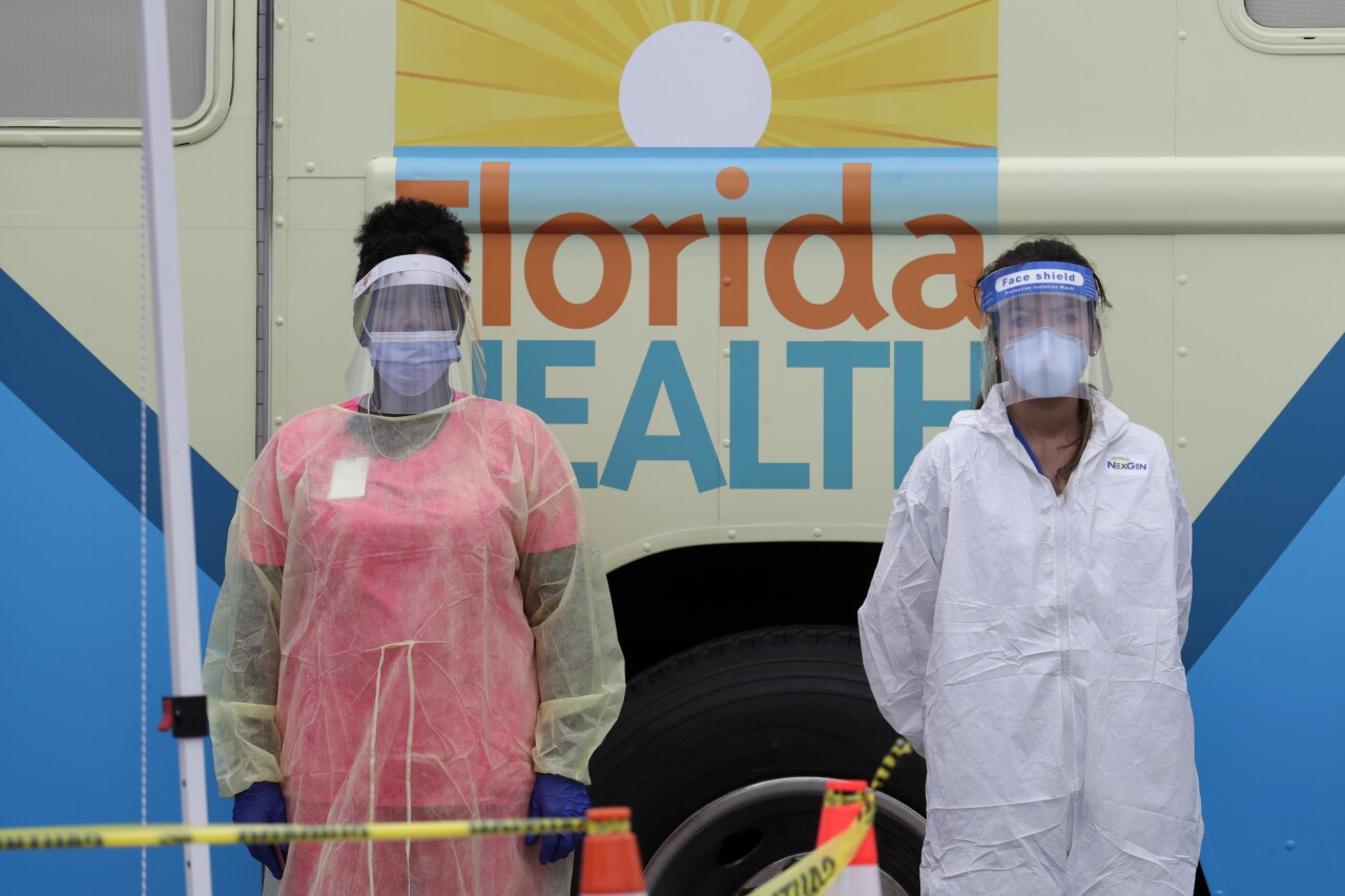 Health workers wearing protective gear in front of mobile coronavirus testing lab