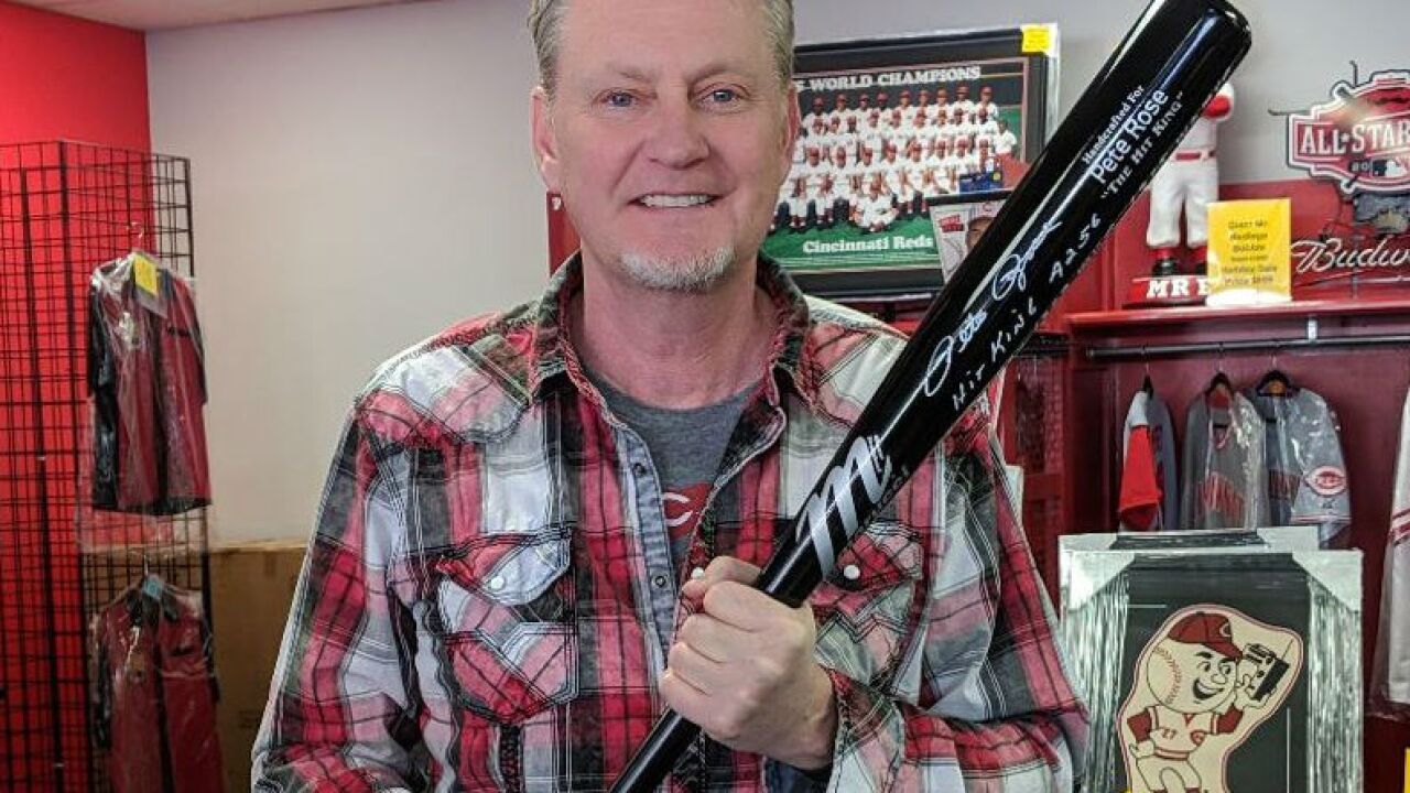 Mark Fugate holds Pete Rose bat that was allegedly stolen from his store, then recovered