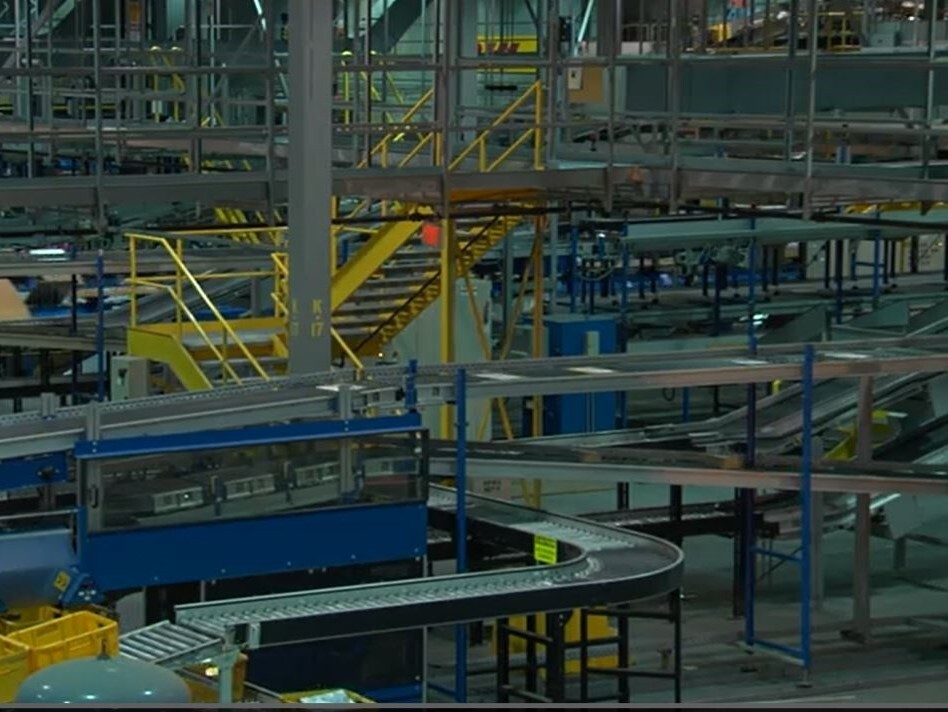 This photo shows the inside of DHL Express operations with many levels of conveyor belts and stairs.