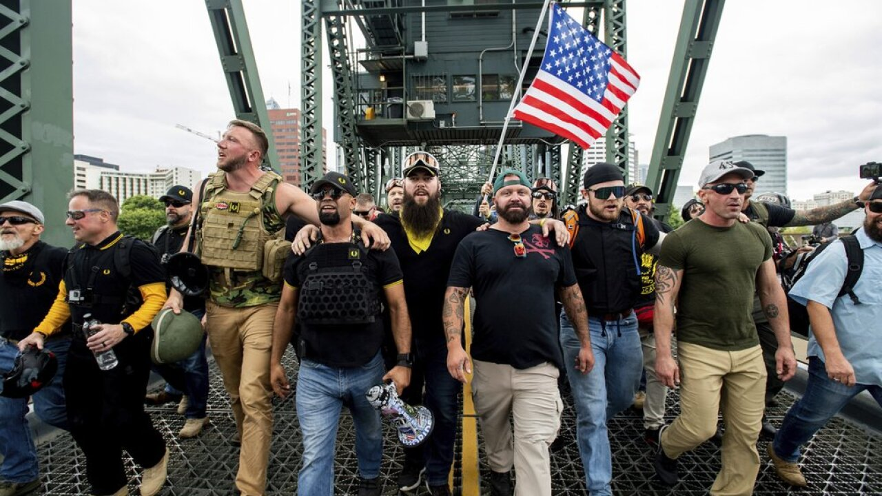 "Members of the Proud Boys and other right-wing demonstrators march across the Hawthorne Bridge during an ""End Domestic Terrorism"" rally in Portland, Ore., on Saturday, Aug. 17, 2019. The group includes organizer Joe Biggs, in green hat, and Proud Boys Chairman Enrique Tarrio, holding megaphone. (Courtesy AP)"